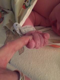 Madelyn holding Josh's finger